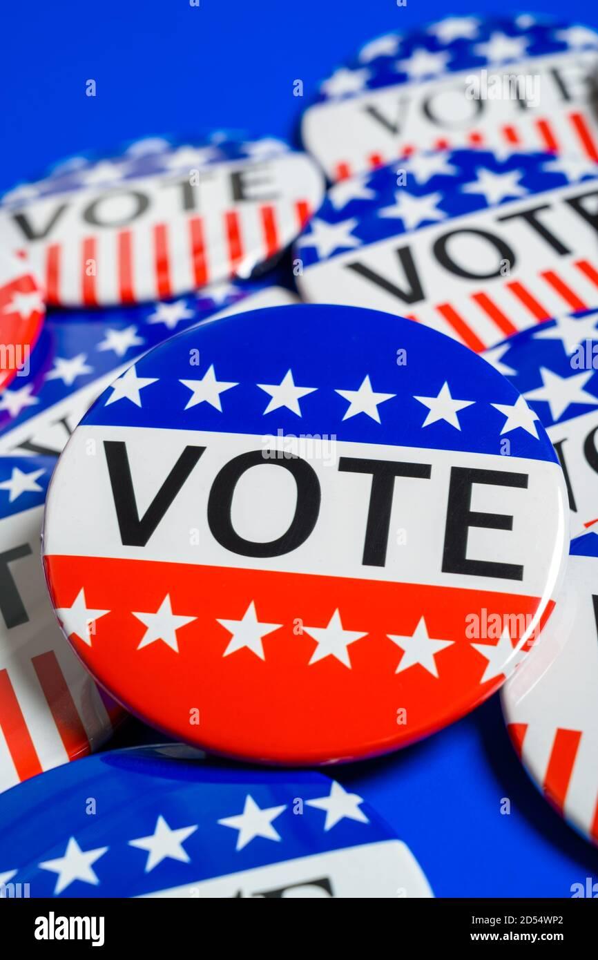Un groupe de boutons de VOTE rouge, blanc et bleu sur fond bleu Banque D'Images