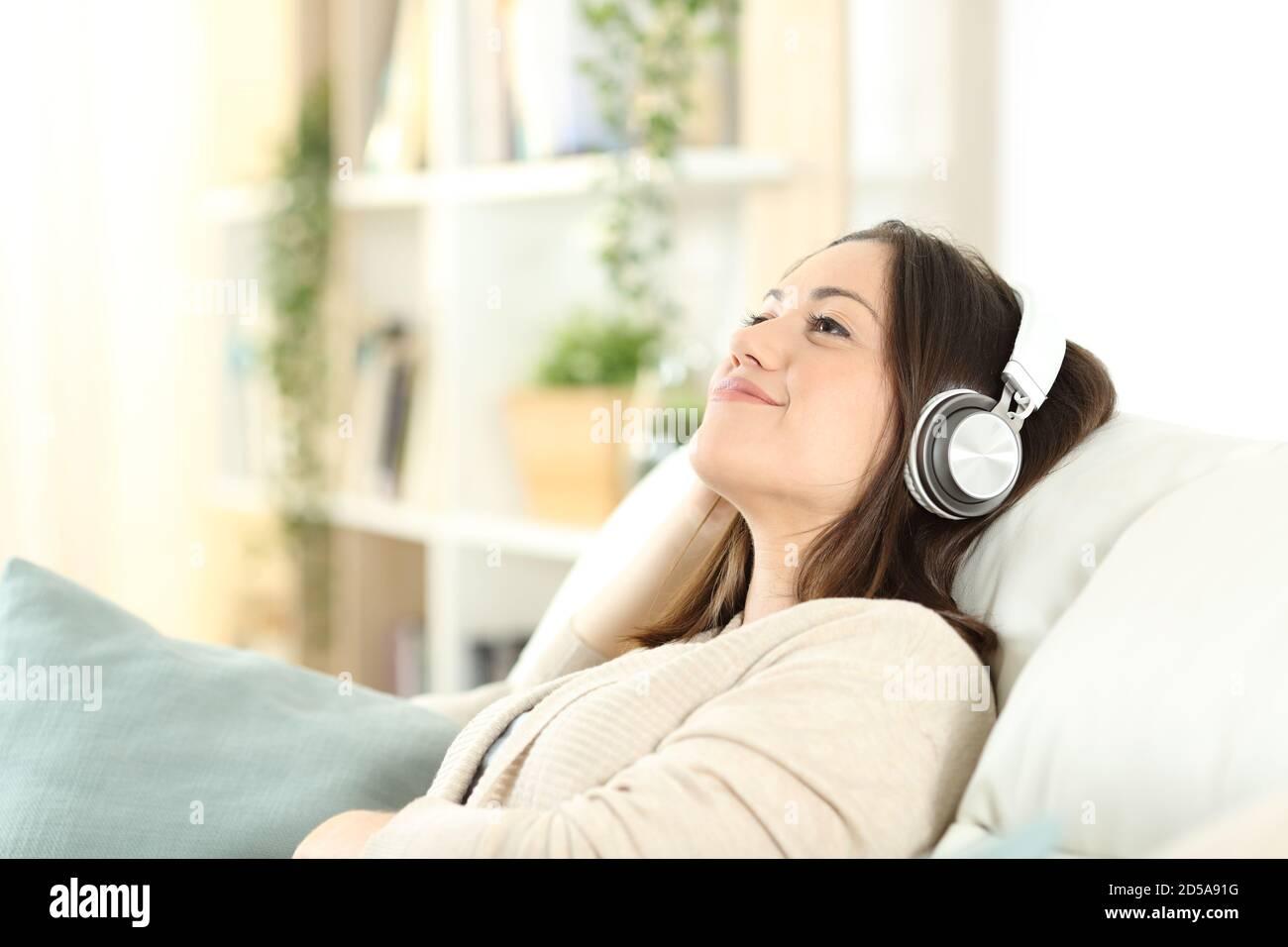 Une femme satisfaite se détendant sur un canapé pour écouter de la musique à la maison Banque D'Images