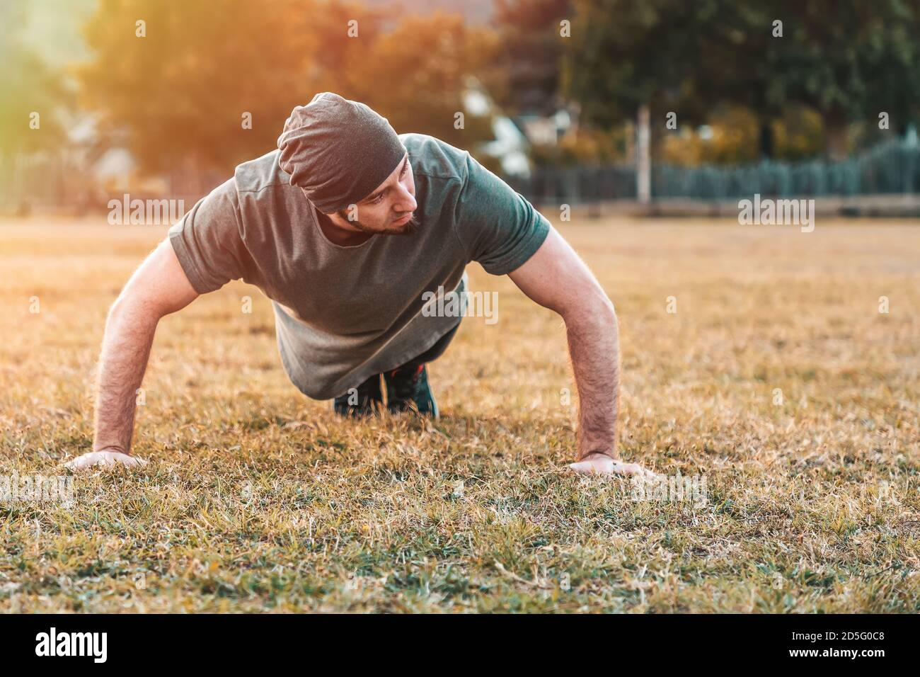 Sports et yoga. Un homme dans les push-up de sport pendant l'entraînement. Parc et arbres en arrière-plan. Copier l'espace. Banque D'Images