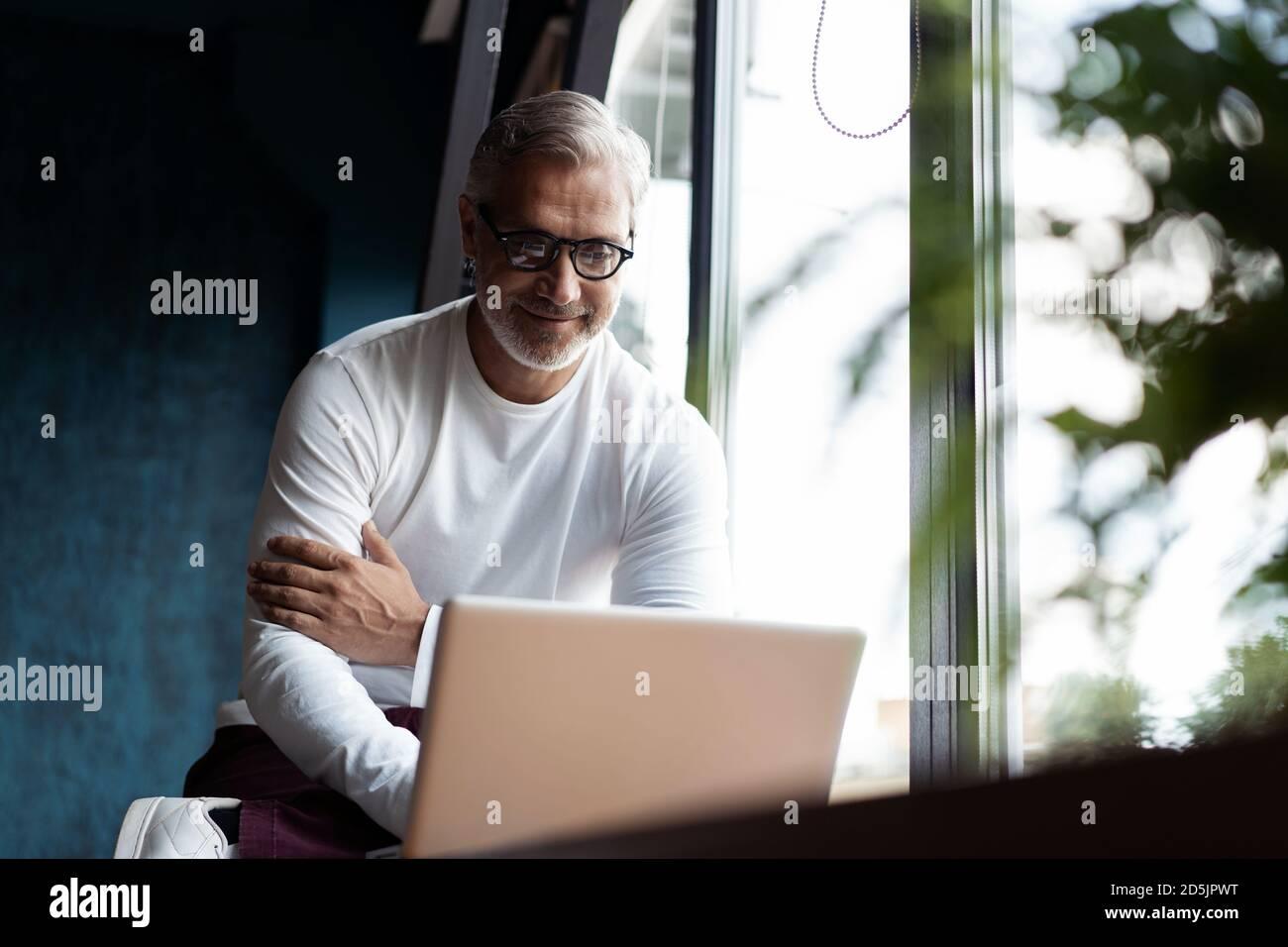 Décontracté gris-cheveux homme mature dans des lunettes de vue travaillant sur ordinateur portable pendant assis dans un bureau ou un café près de la fenêtre Banque D'Images