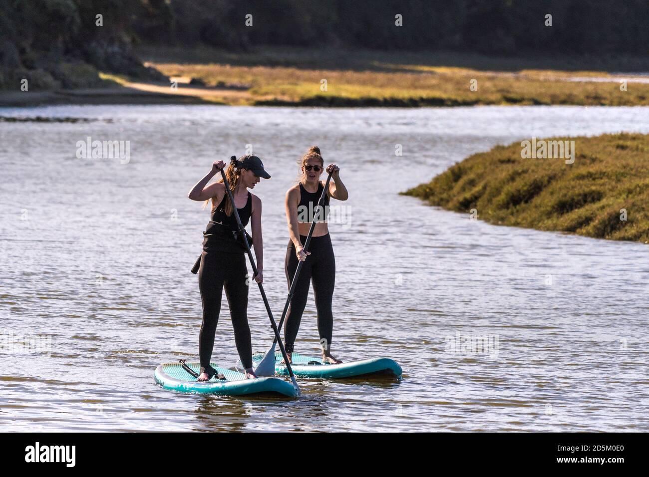Deux femmes en vacances debout sur des planches à pédales Stand Up et pagayant sur la rivière Gannel à Newquay, en Cornouailles. Banque D'Images