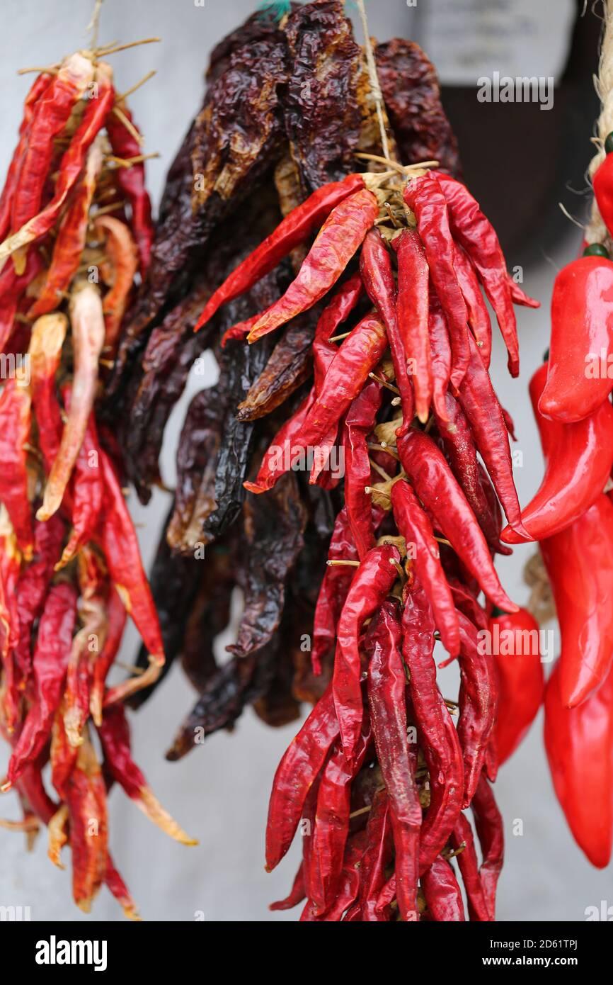 Bouquet de poivrons rouges de lanterne au piment. Une pile de poivrons rouges est suspendue sur un stand de marché. Poivron rouge séché accroché au mur Banque D'Images