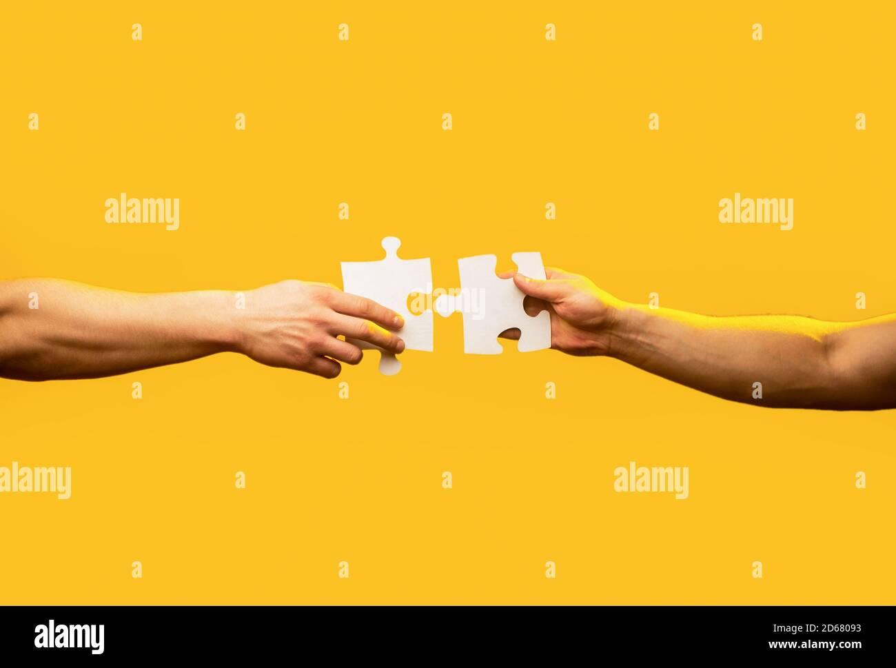 Pièce de puzzle main homme reliant couple. Solutions d'affaires, cible, succès, objectifs et concepts de stratégie. Puzzle à connexion manuelle. Entreprise Banque D'Images
