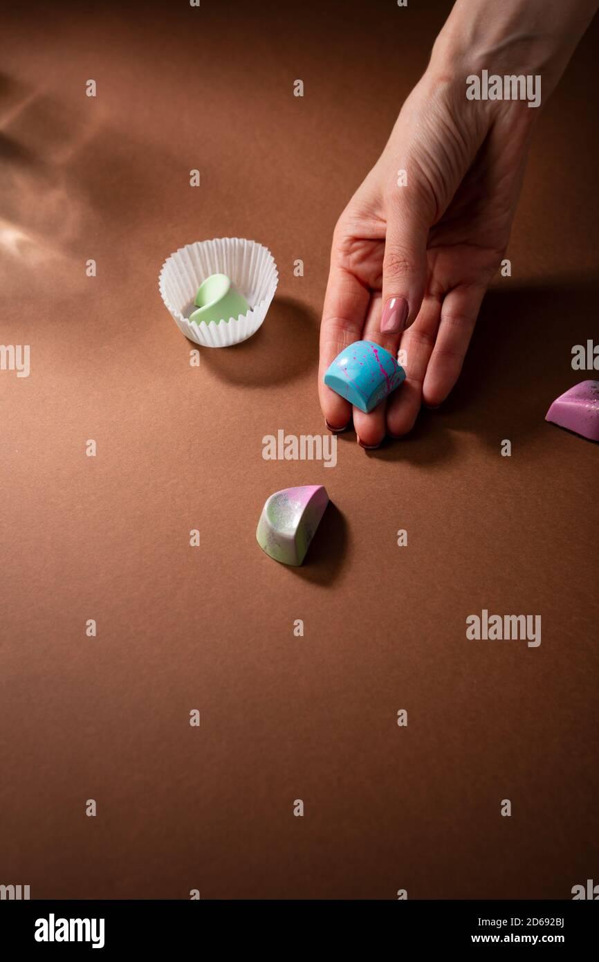 Bonbons au chocolat à la main sur une surface brune Banque D'Images