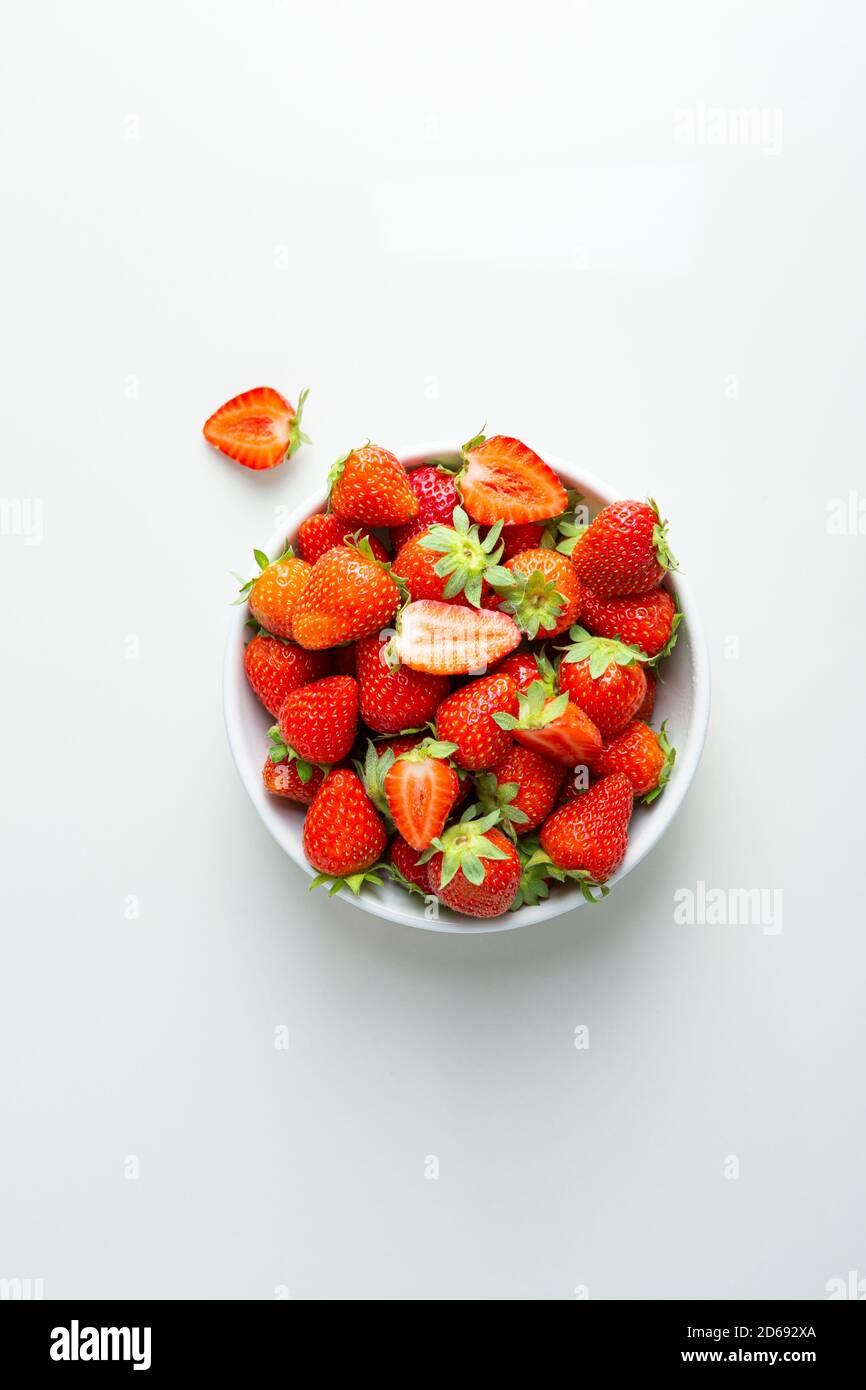 Vue en hauteur d'un bol de fraise ou d'une table blanche Banque D'Images