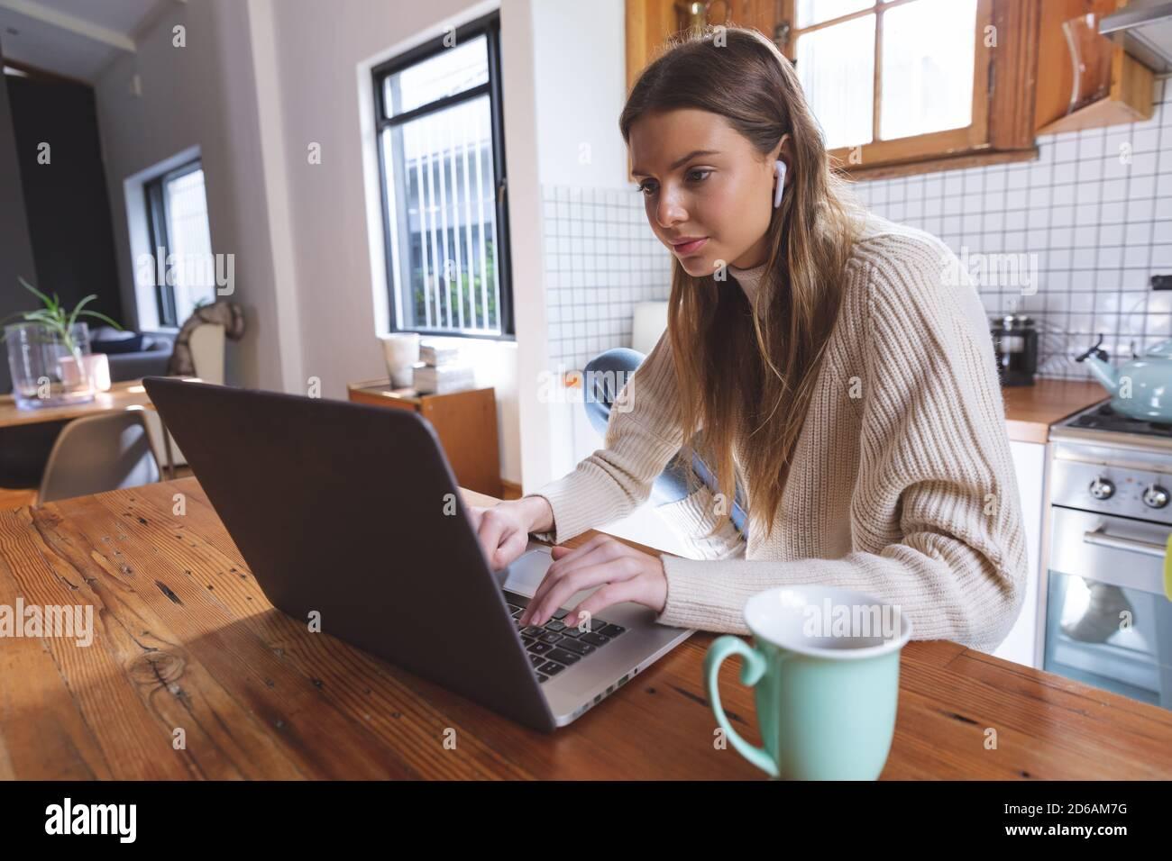 Woman using laptop in La cuisine à la maison Banque D'Images