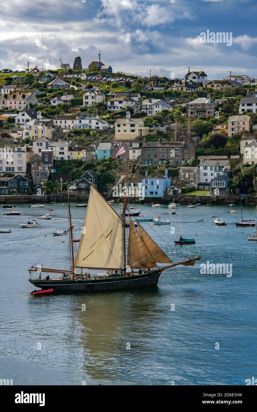 Vieux ketch quittant Fowey Harbour avec la ville de Poltuan derrière Cornwall Angleterre Banque D'Images