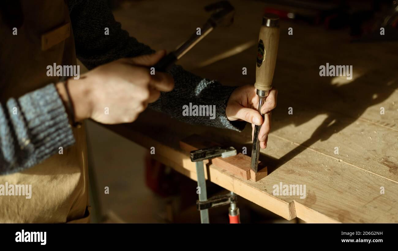 Gros plan des mains de charpentier travaillant avec un marteau dans un petit atelier de menuiserie. Jeune femme travailleuse de bois travaillant sur un morceau de bois pour une nouvelle maison d Banque D'Images