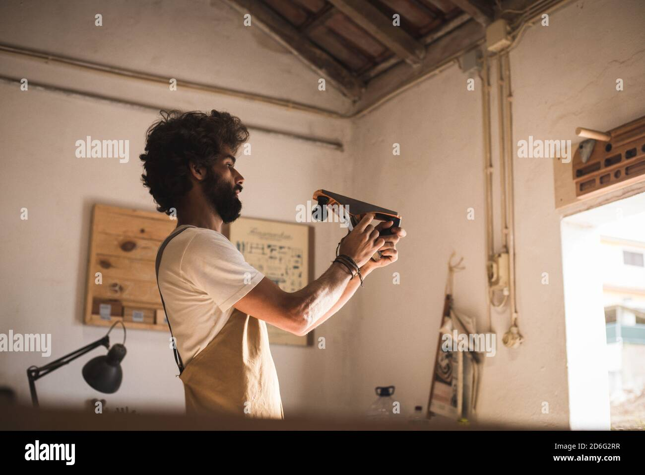 Homme hispanique travaillant comme menuisier dans un petit laboratoire de bois. L'homme barbu s'est concentré sur la mise en forme d'un nouveau morceau de bois pour un mobilier de maison dans sa ca Banque D'Images
