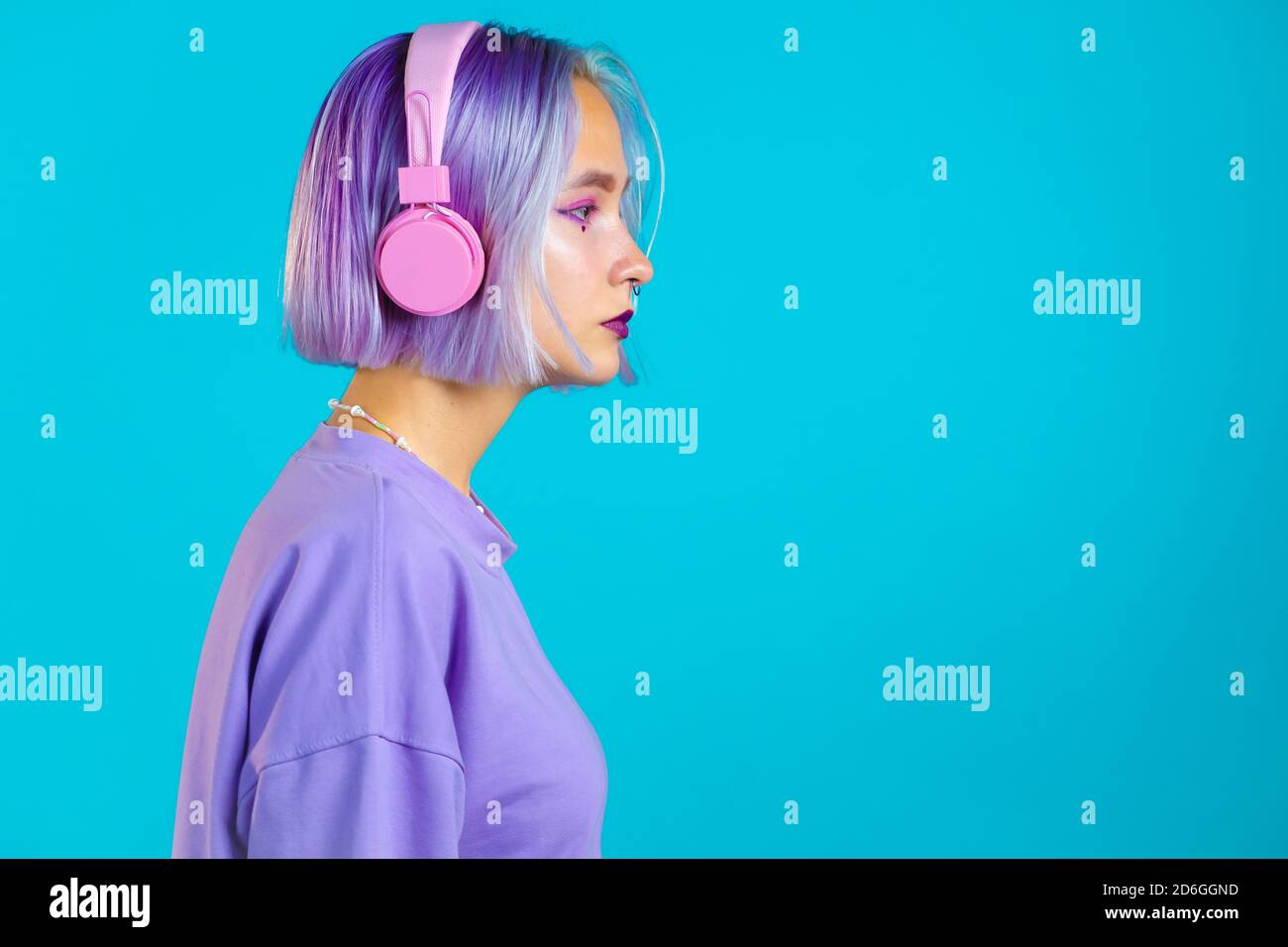 Jolie fille aux cheveux violets teints écoutant de la musique, souriant, dansant dans un casque en studio sur fond bleu. Musique, danse, concept radio Banque D'Images