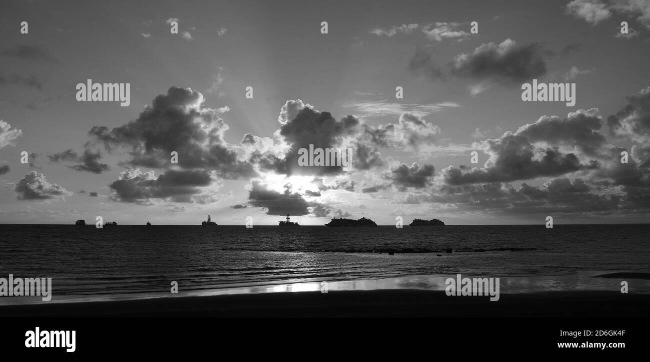 Lever de soleil de la plage avec des navires à l'horizon et ciel avec nuages épars Banque D'Images