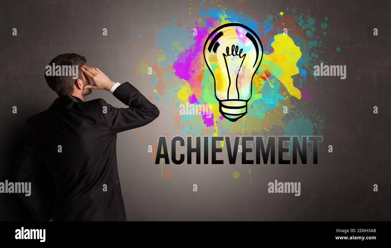 Homme d'affaires tirant une ampoule colorée avec inscription DE RÉALISATION sur un mur en béton texturé, nouveau concept d'idée d'affaires Banque D'Images