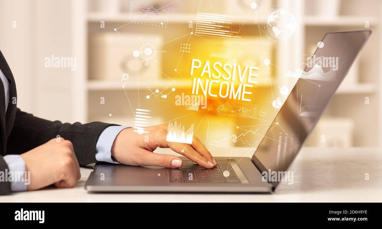 Vue latérale d'un professionnel travaillant sur un ordinateur portable avec inscription PASSIVE DU REVENU, concept d'entreprise moderne Banque D'Images