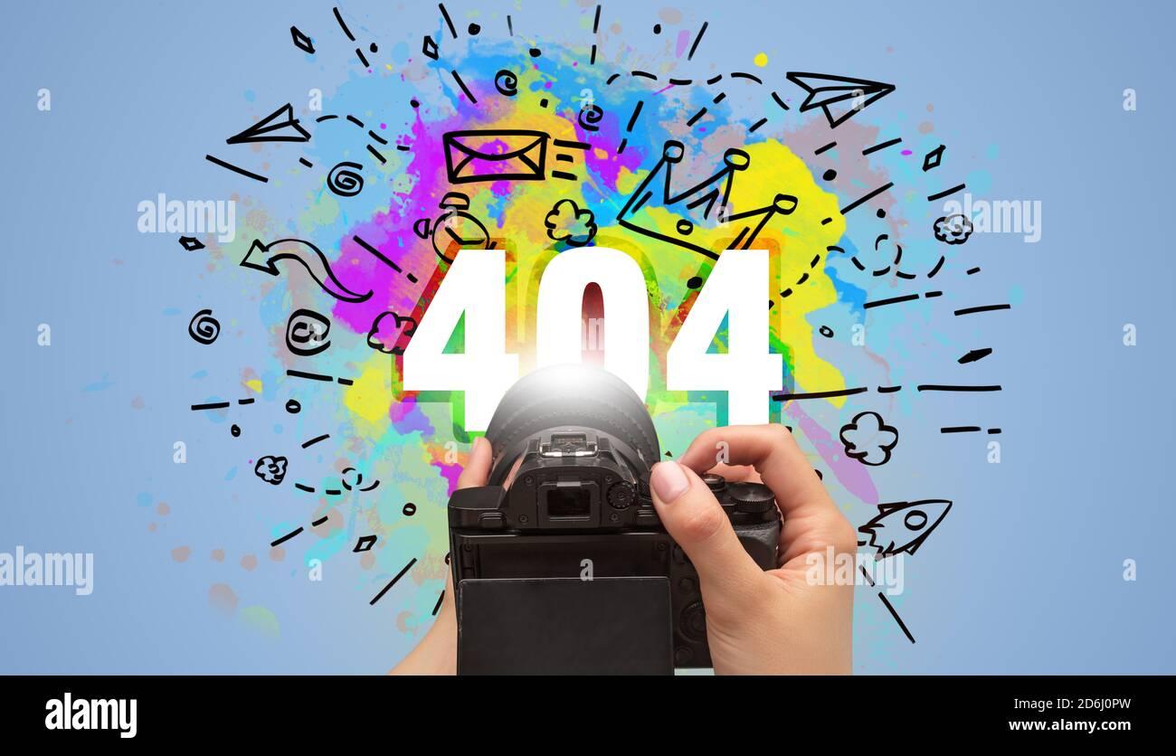 Gros plan d'une main tenant un appareil photo numérique avec dessin abstrait et inscription 404 Banque D'Images