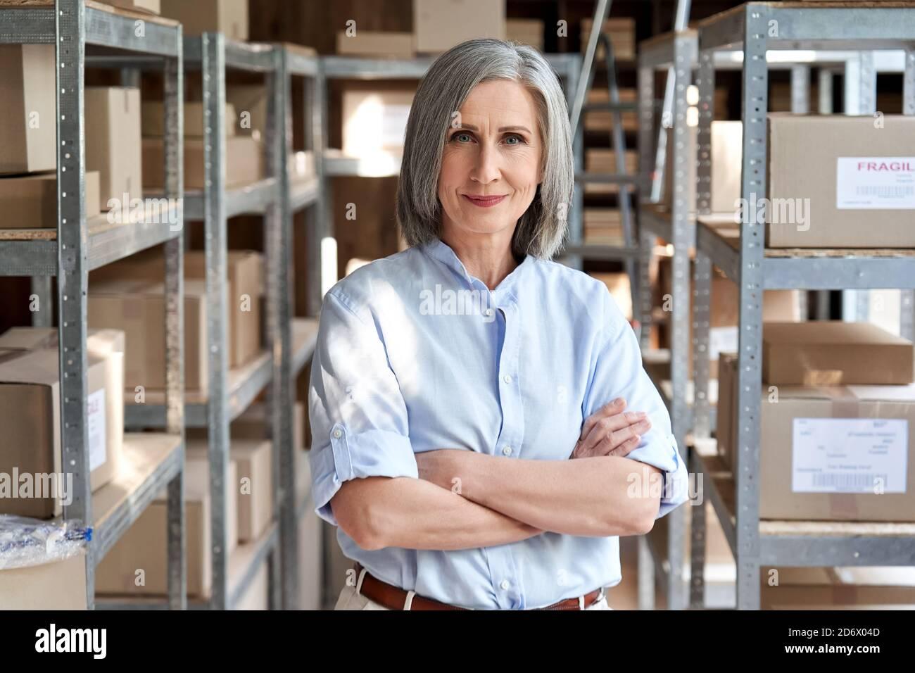 Femme confiante gérant debout dans l'entrepôt d'expédition de livraison, portrait. Banque D'Images