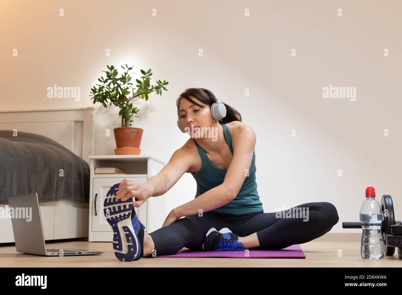De belles femmes qui font de la remise en forme à la maison près du lit et regarder des tutoriels en ligne sur ordinateur portable dans la lumière naturelle. Concept de sport et de loisirs. Banque D'Images