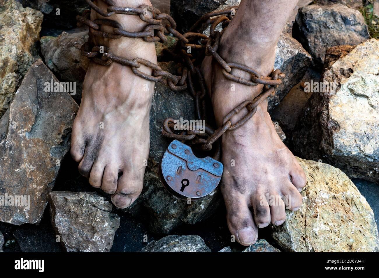 Les pieds sales de l'esclave sont enroulés dans une chaîne rouillée avec une grande serrure. Concept de travail esclave Banque D'Images