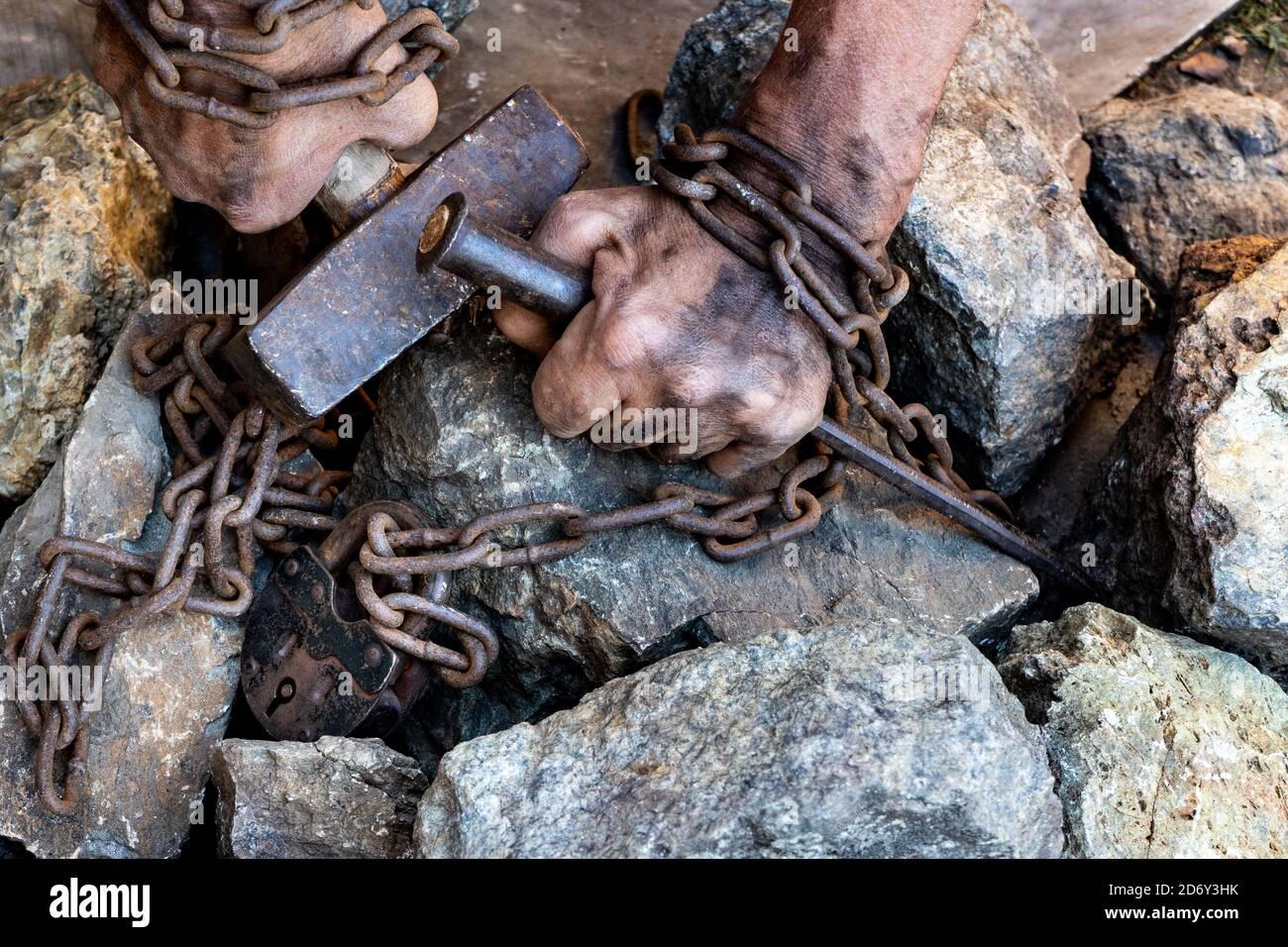 Les mains sales d'un esclave tenant un marteau sont enroulés dans une chaîne rouillée avec un grand cadenas sur un fond de pierres. Banque D'Images