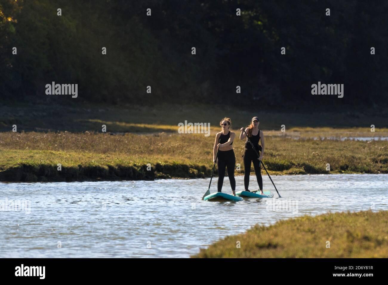 Deux femmes de vacances sur les paddleboards Stand Up paddle long de la rivière Gannel dans la lumière du début de soirée à Newquay, dans les Cornouailles. Banque D'Images