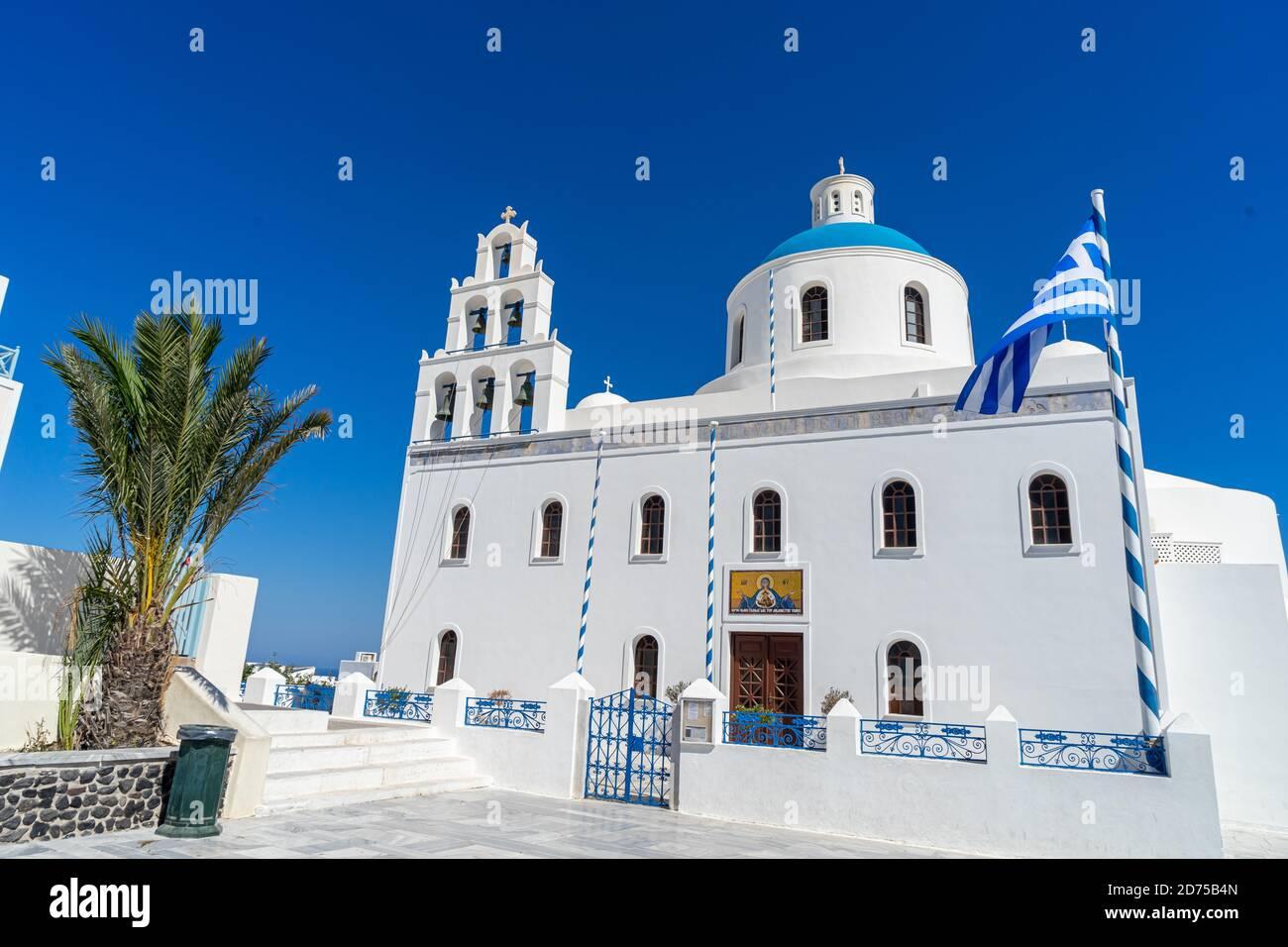 Eglise orthodoxe à Oia, Santorin, Grèce, un jour d'été avec drapeau grec. Beau ciel bleu clair. Banque D'Images