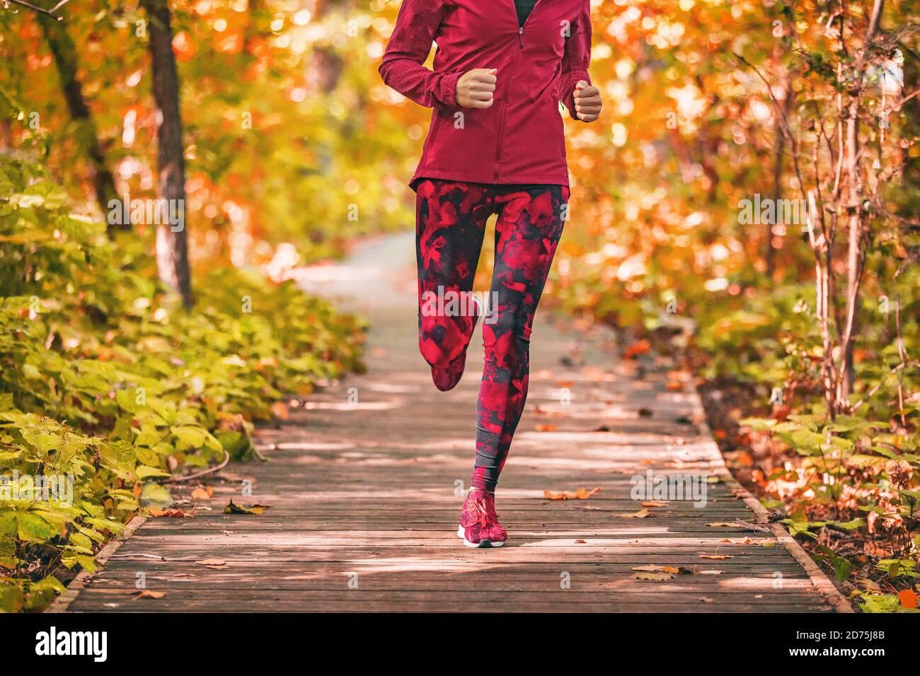 Sentier de course femme courir dans la forêt parc nature plein air entraînement de fitness sur la promenade en automne feuillage portant des vêtements d'activewear rouge. Fille Banque D'Images