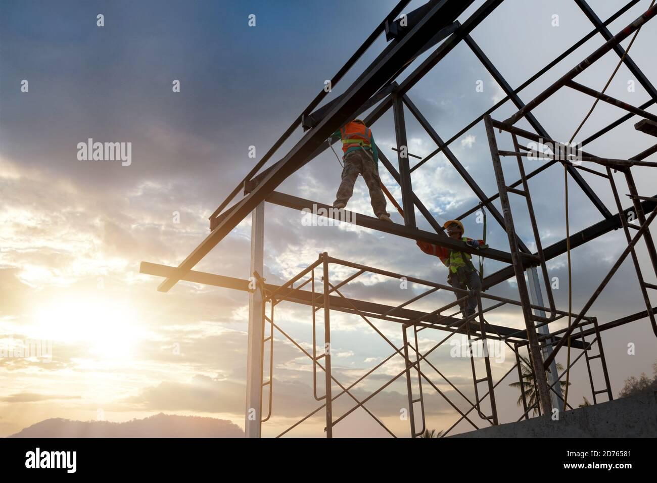 Silhouette d'ouvrier de construction sur la structure de toit dans le chantier de construction, concept équipement de hauteur de sécurité. Banque D'Images