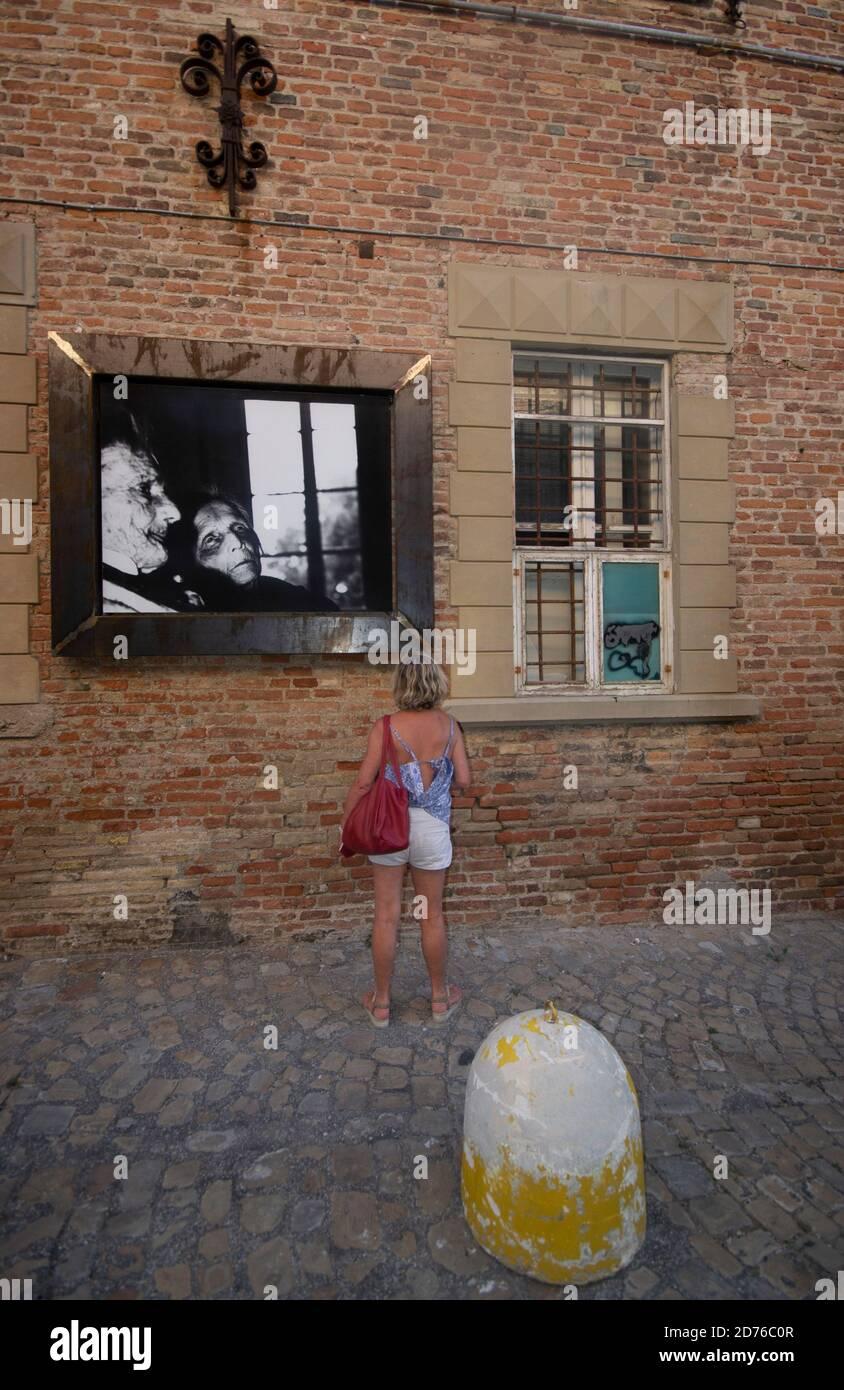 Un touriste observe l'un des magnifiques noirs et blancs de Giacomelli Photos affichées le long des rues de Mondolfo Banque D'Images