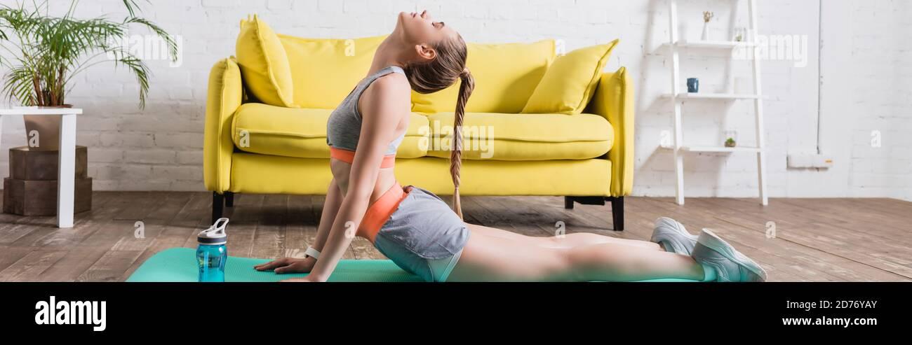 Photo panoramique de sportswoman s'étendant sur un tapis de fitness à la maison Banque D'Images