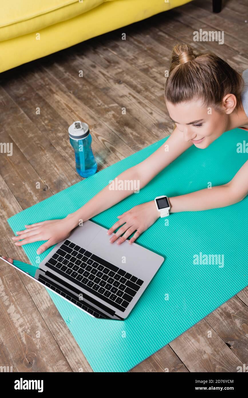 Smiling sportswoman utilisant un ordinateur portable sur un tapis de fitness à la maison Banque D'Images