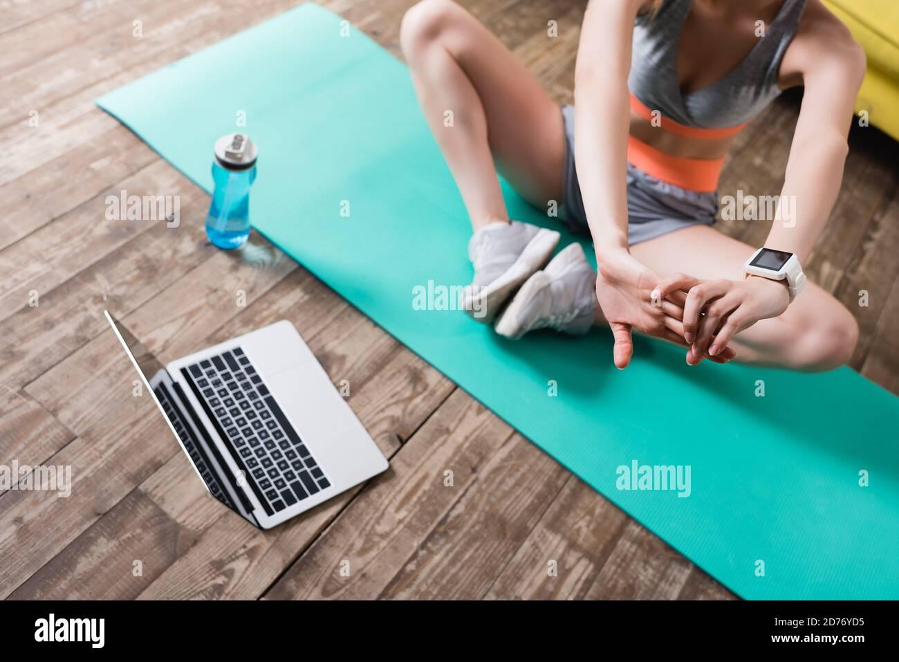 Vue rognée de sportswoman s'étendant près d'un ordinateur portable et d'une bouteille de sport à la maison Banque D'Images