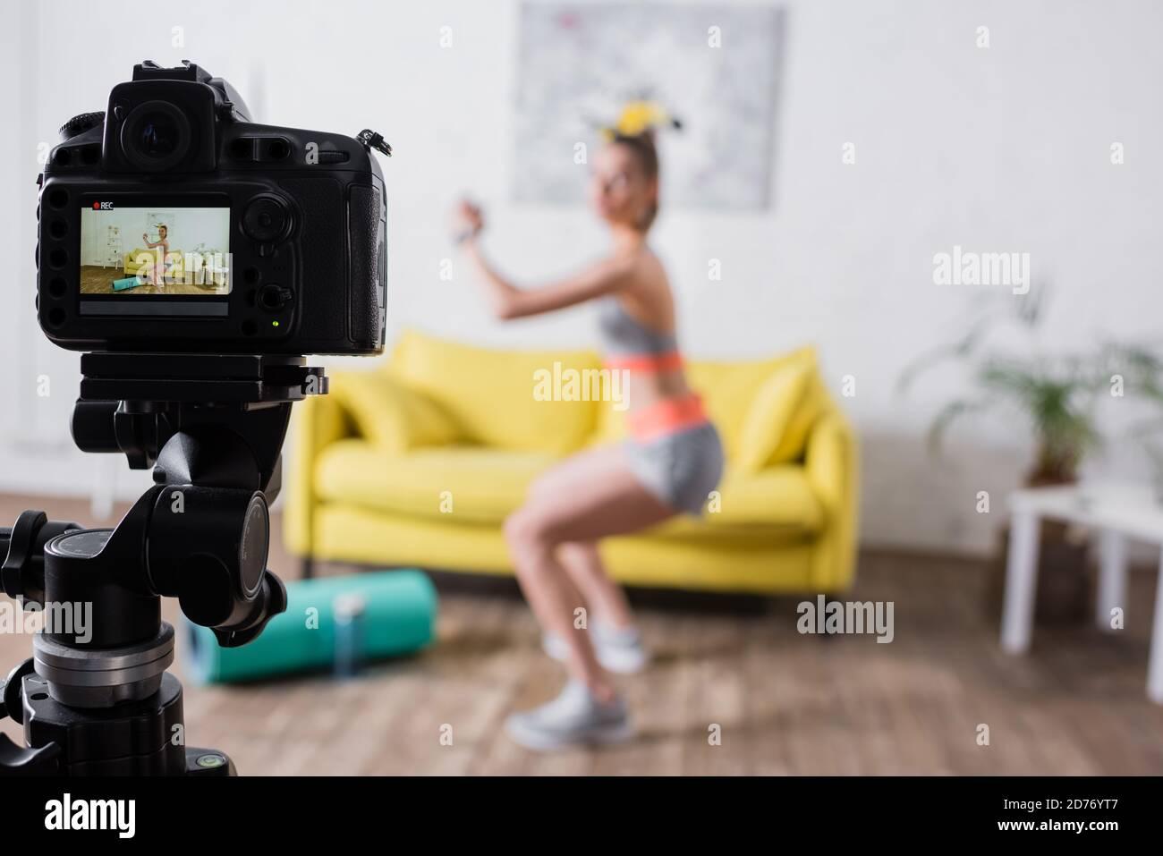 Objectif sélectif de la jeune sportswoman formation près de l'appareil photo numérique dans séjour Banque D'Images