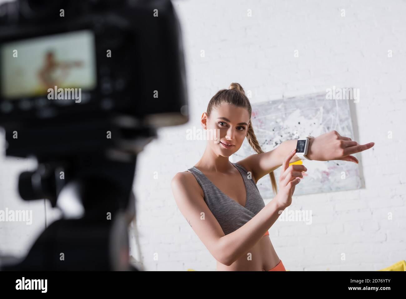 Mise au point sélective d'une sportswoman souriante pointant vers une montre intelligente à proximité appareil photo numérique à la maison Banque D'Images