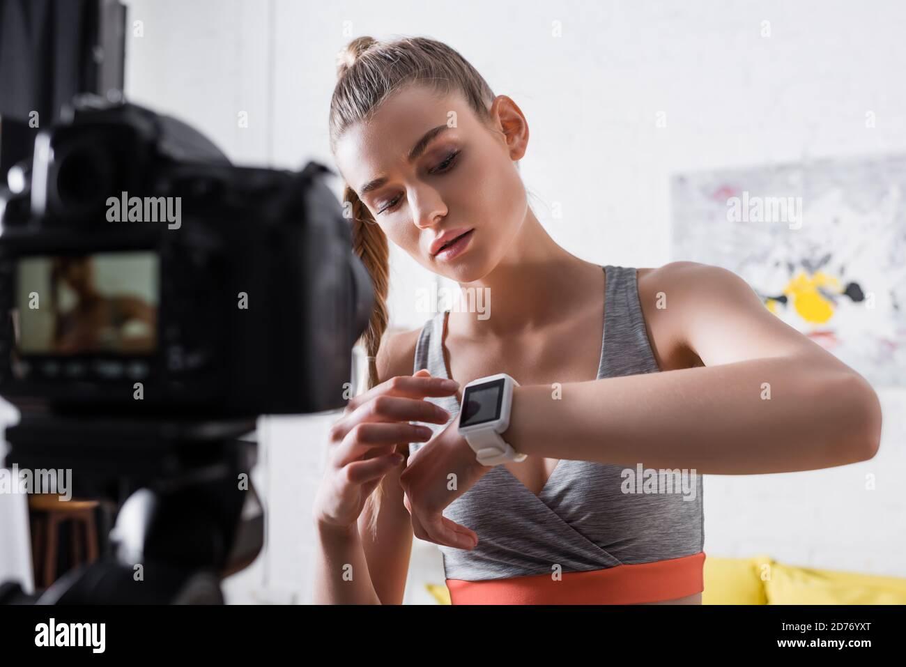 Objectif sélectif de la femme dans les vêtements de sport pointant vers le tracker de forme physique près de l'appareil photo numérique à la maison Banque D'Images