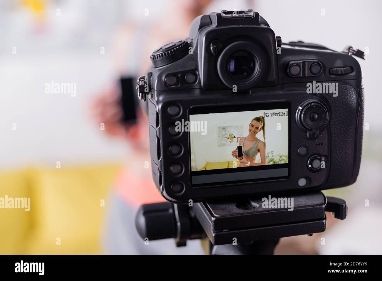 Mise au point sélective d'un smartphone sportswoman souriant avec écran vierge près de l'appareil photo numérique Banque D'Images