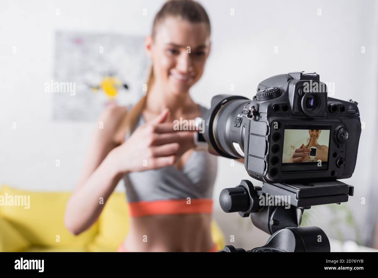 Mise au point sélective d'une sportswoman souriante pointant vers une montre intelligente proche du numérique appareil photo Banque D'Images