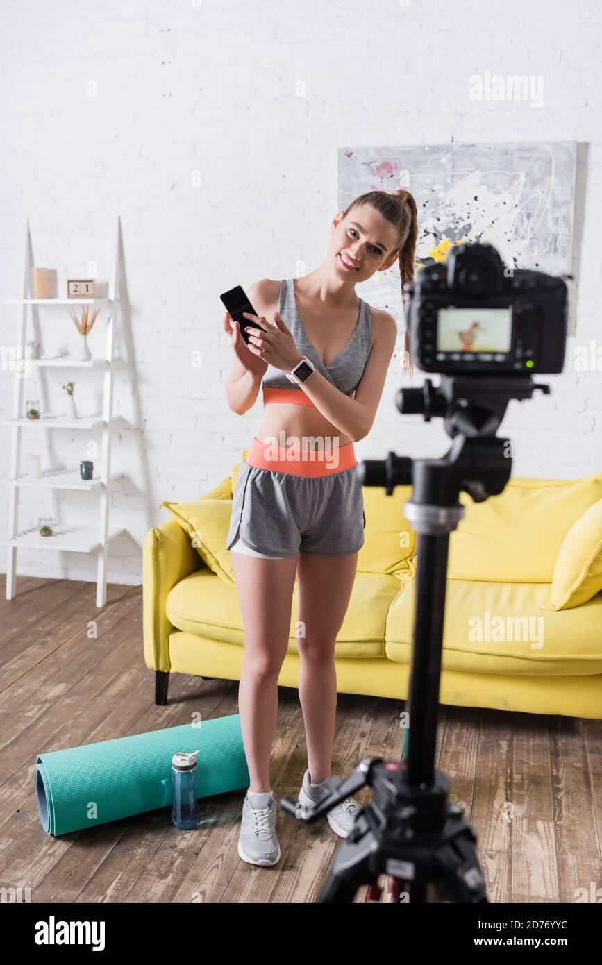 Mise au point sélective d'une sportswoman souriante pointant vers un smartphone proche du numérique appareil photo et tapis de fitness à la maison Banque D'Images
