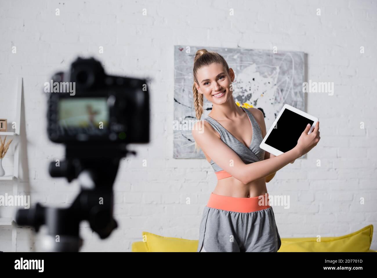 Mise au point sélective d'une tablette numérique positive sportswoman avec cache écran près de l'appareil photo numérique à la maison Banque D'Images