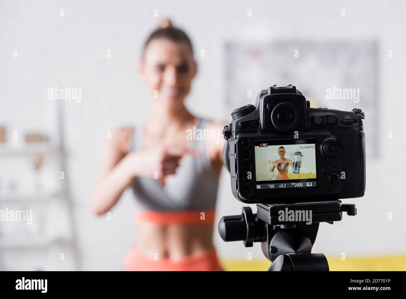 Mise au point sélective d'une sportswoman souriante pointant vers une bouteille de sport à proximité appareil photo numérique Banque D'Images