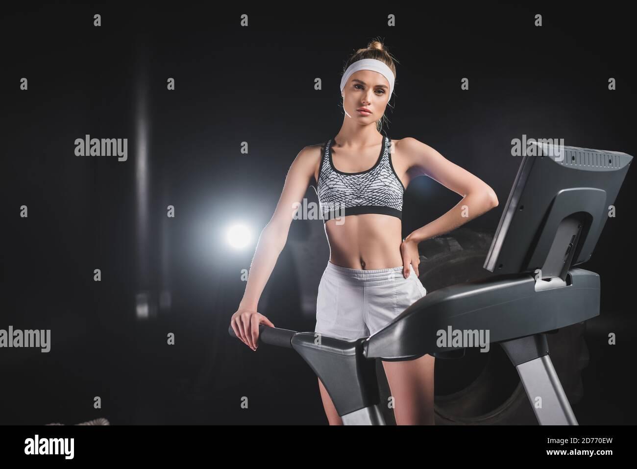 Jeune sportswoman avec main sur la hanche regardant l'appareil photo allumé tapis roulant dans la salle de gym Banque D'Images