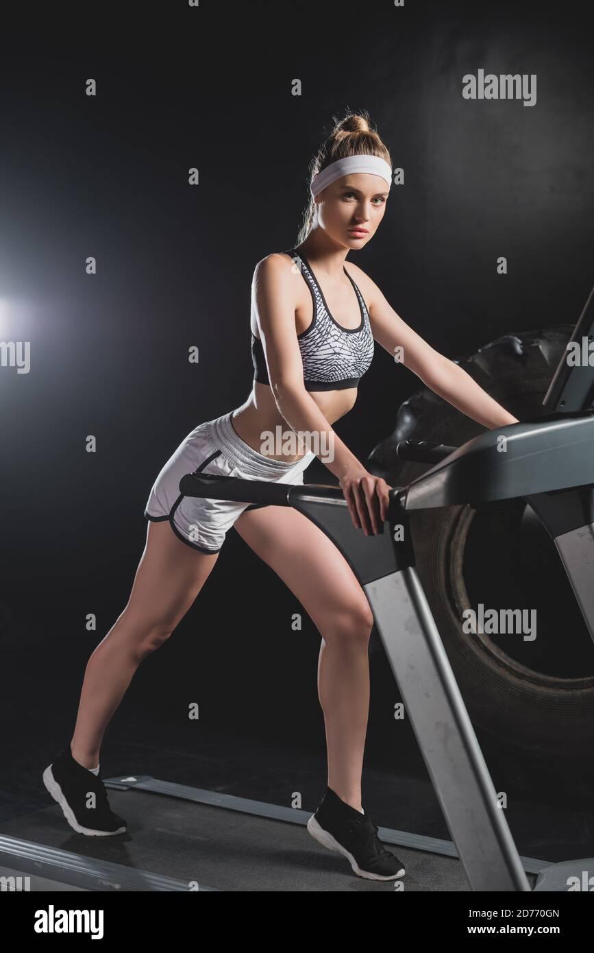 Jeune sportswoman regardant l'appareil photo tout en courant sur un tapis roulant dedans salle de sport Banque D'Images