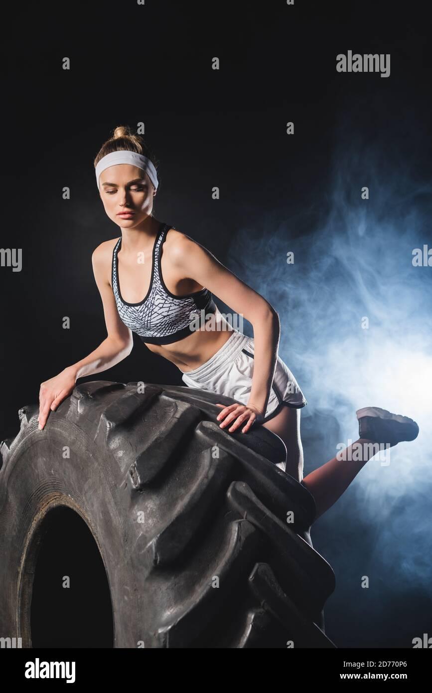 Objectif sélectif de jeune sportswoman touchant le pneu dans la salle de sport avec fumée Banque D'Images