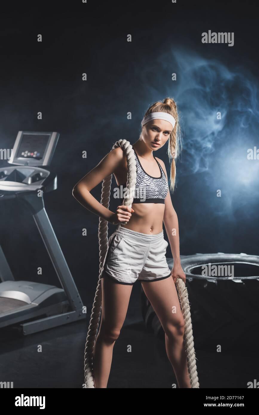 Mise au point sélective de sportswoman avec corde de bataille regardant la caméra près de pneu et tapis roulant dans la salle de gym avec fumée Banque D'Images