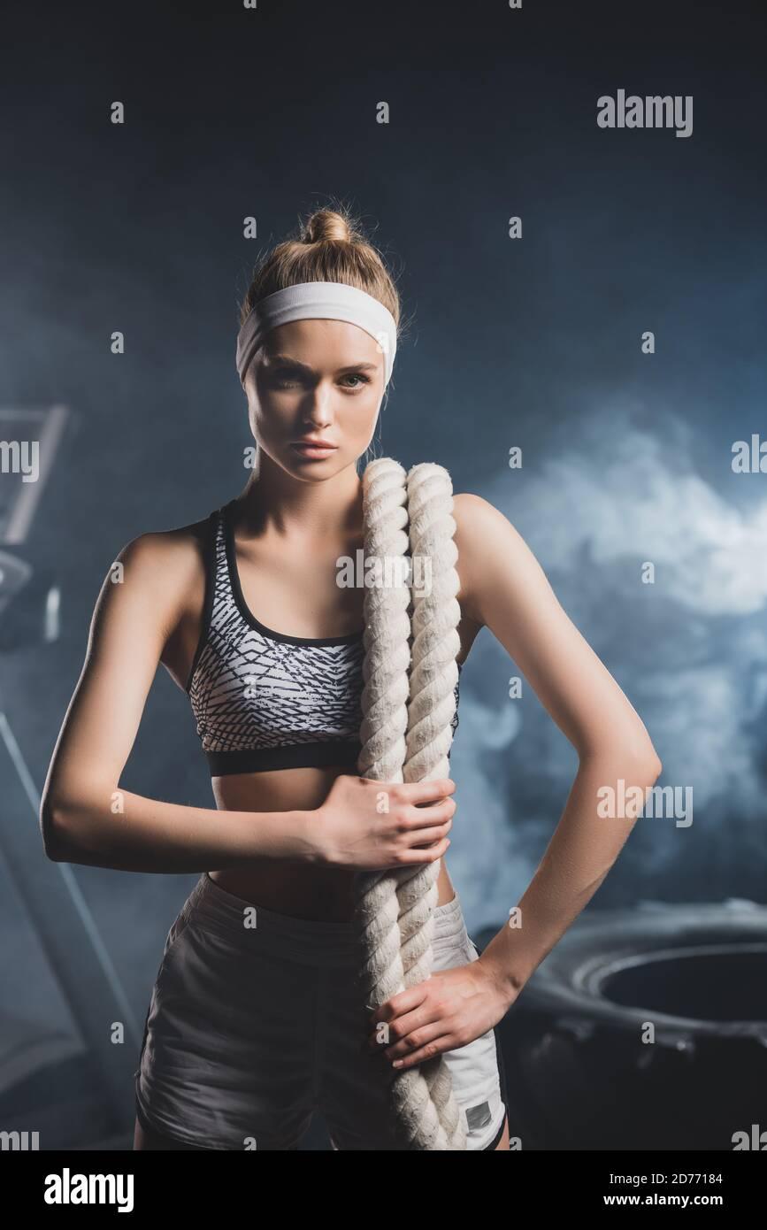 Jeune sportswoman avec corde de bataille regardant la caméra dans le sport centre avec fumée Banque D'Images