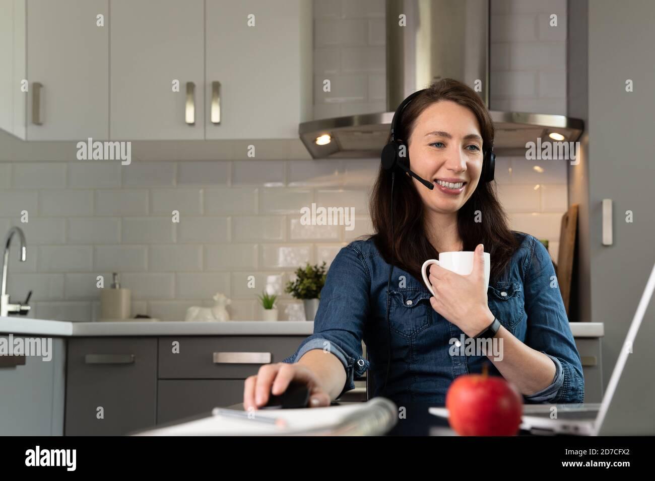 Les femmes participent à une conférence téléphonique et affichent leur plan d'entreprise sur un tableau blanc pour enfants. Concept de travail à domicile. Banque D'Images