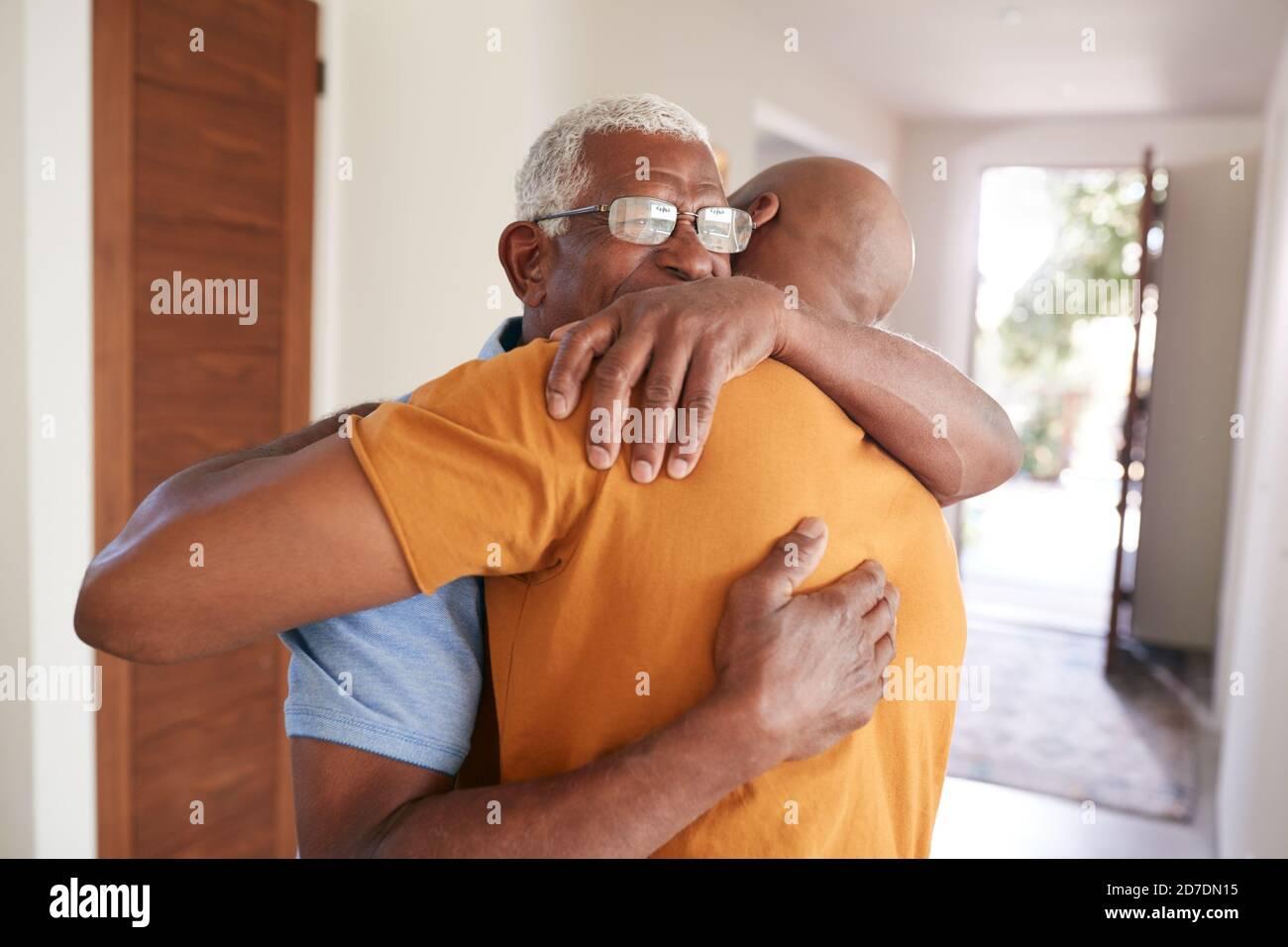 Père aîné aimant embrassant un fils adulte à l'intérieur à la maison Banque D'Images