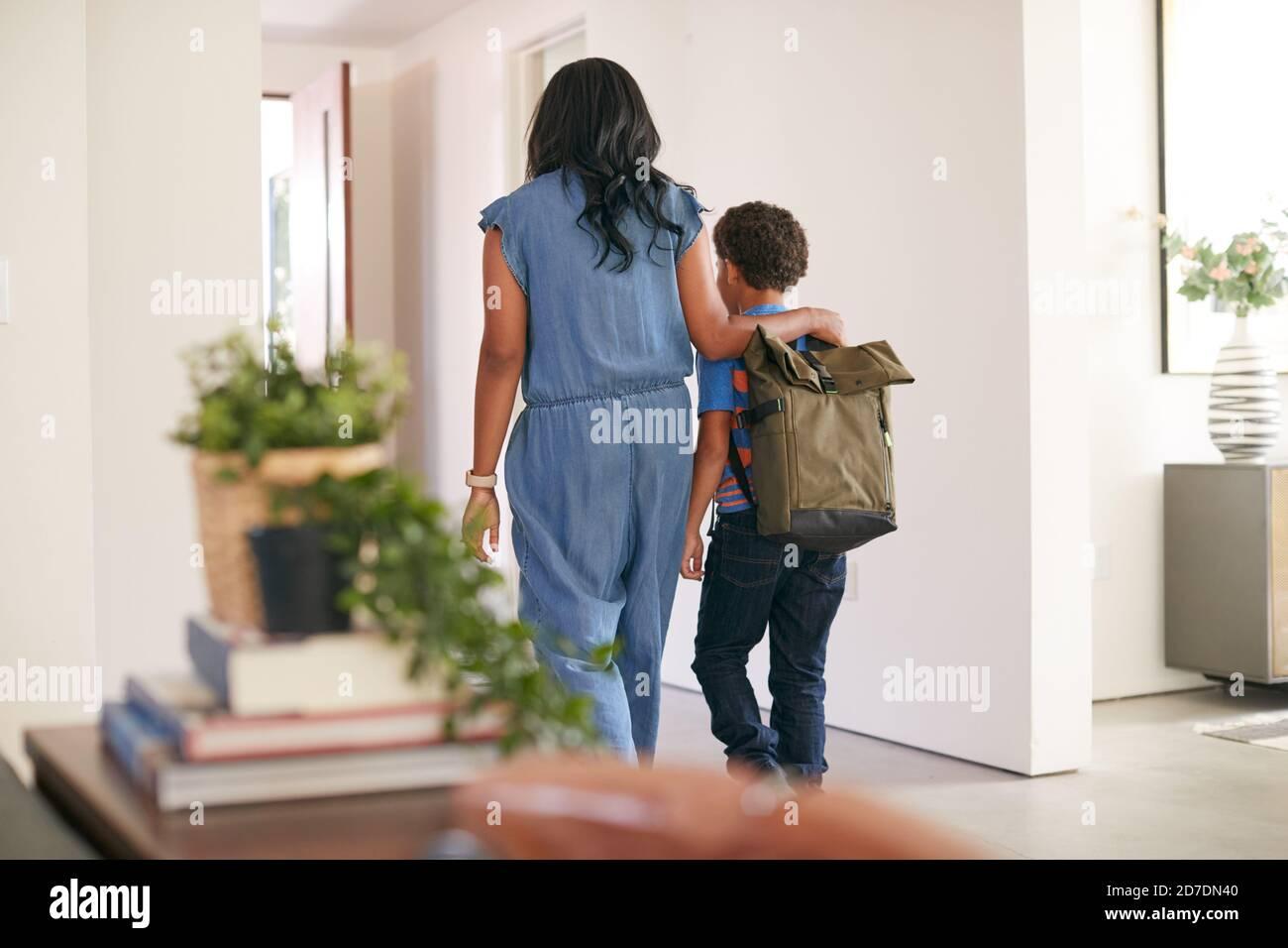 Vue arrière de mère disant Au revoir à fils comme lui Quitte la maison pour l'école Banque D'Images