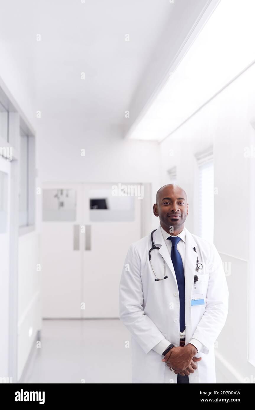 Portrait d'un médecin de sexe masculin mature portant une couche blanche debout Couloir de l'hôpital Banque D'Images