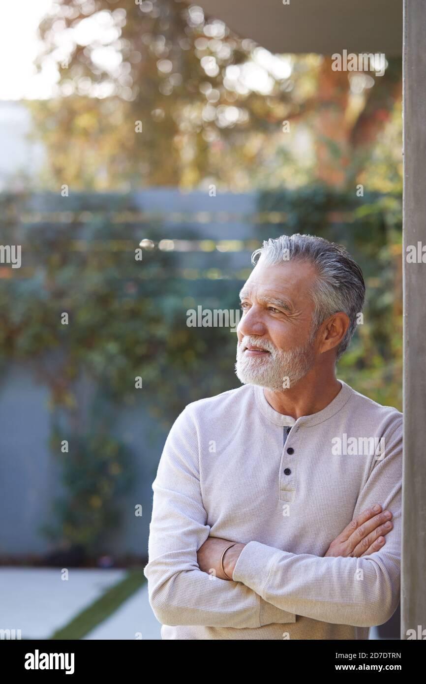 Portrait de l'homme hispanique senior retraité souriant dans le jardin à Accueil contre Flaring Sun Banque D'Images