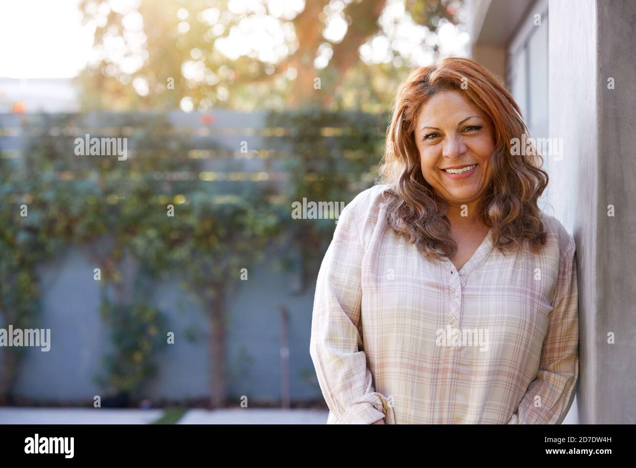 Portrait d'une femme hispanique senior souriante dans le jardin à la maison Contre Flaring Sun Banque D'Images