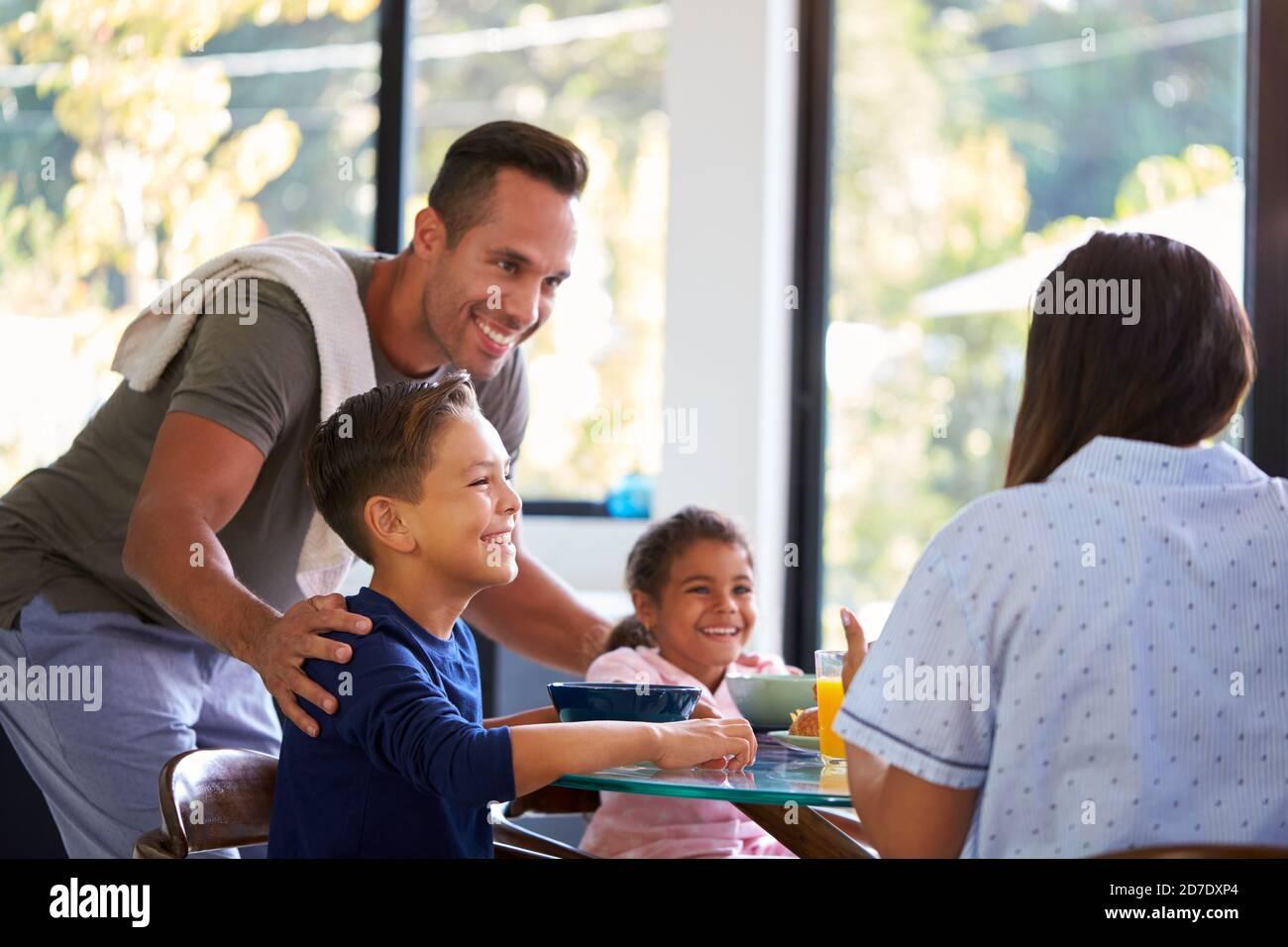 Famille hispanique assis autour de la table manger petit déjeuner ensemble Banque D'Images